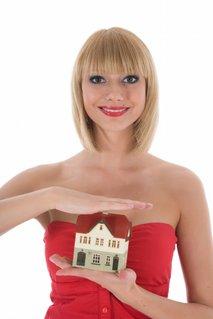 poslovna ženska s hišico v rokah