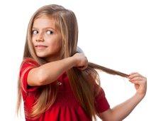 Deklica si češe lase