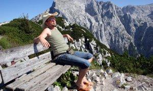 moški na klopi sredi gora