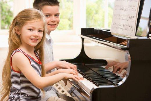 Deček in deklica ob klavirju