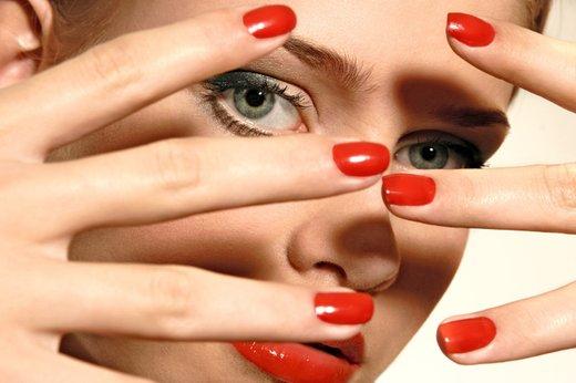 ženska z rdeče lakiranimi nohti
