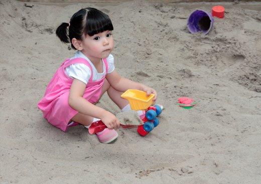 Deklica se igra v peskovniku