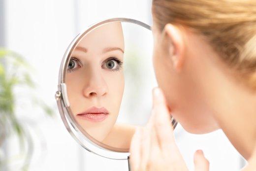 ženska se gleda v ogledalu