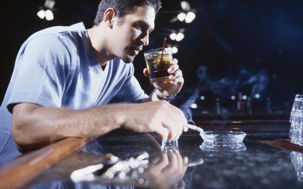moški kadi in pije alkohol