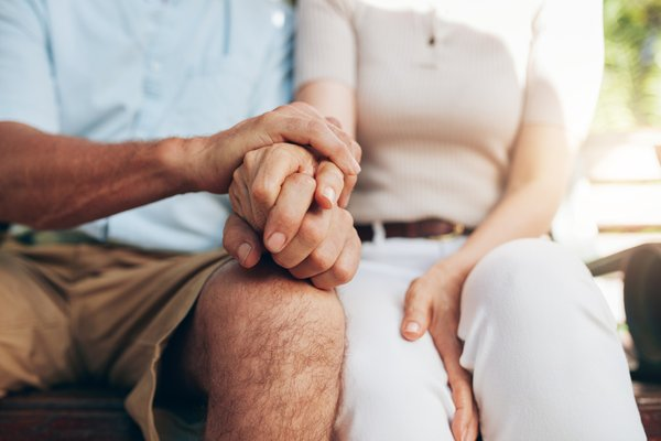 starejši par se drži za roke