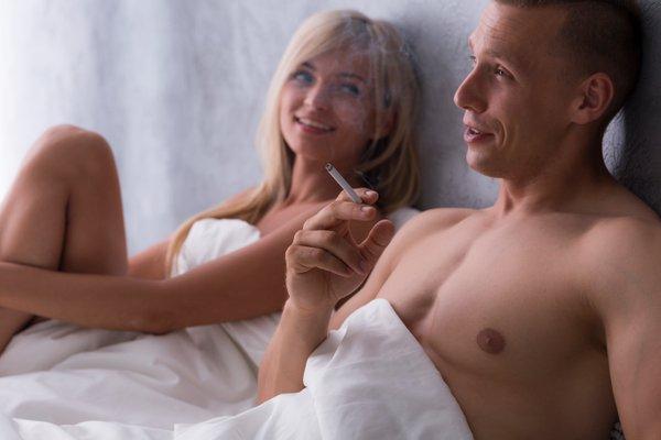 moški kadi v postelji z žensko