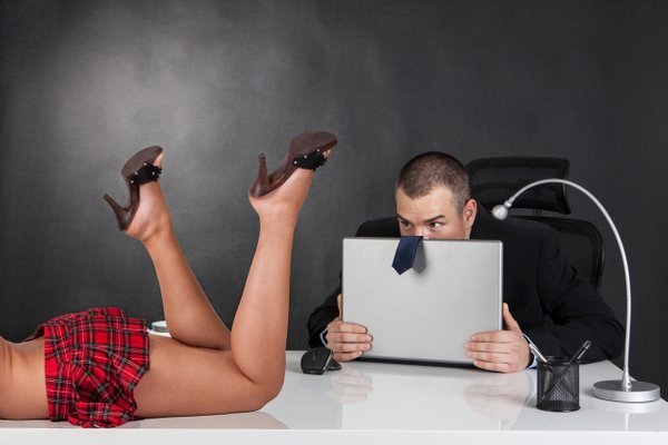 moški v pisarni opazuje seksi sodelavko