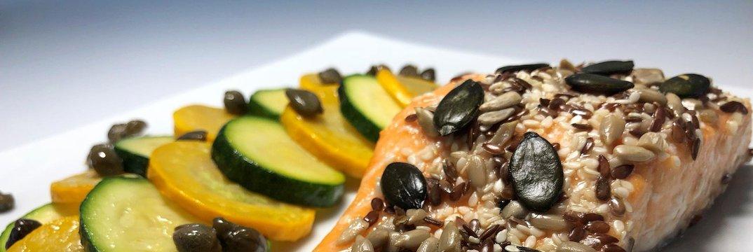 V pečici pečen losos s semeni in pražene bučke