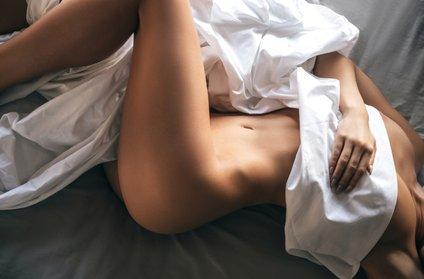 Gola ženska v postelji
