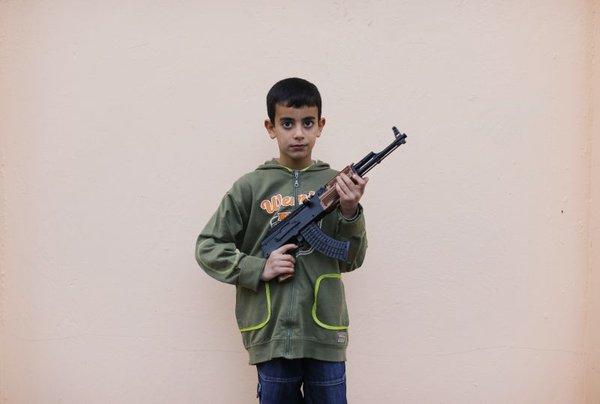 Devetletni sirski deček z avtomatsko puško