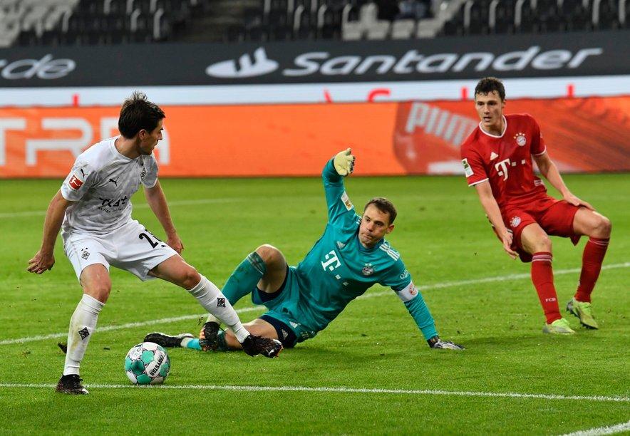 Jonas Hofmann (z žogo) poskuša zadeti ob vratarju Bayerna Manuelu Neuerju in branilcu državnih ter evropskih prvakov Benjaminu Pavardu. V petek je mrežo Bavarcev zatresel dvakrat.