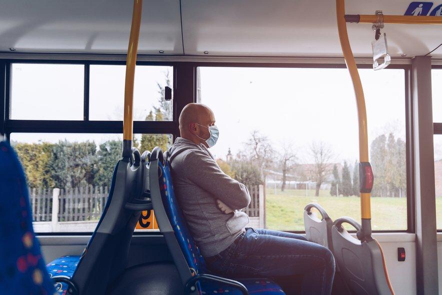 Moški z masko na avtobusu