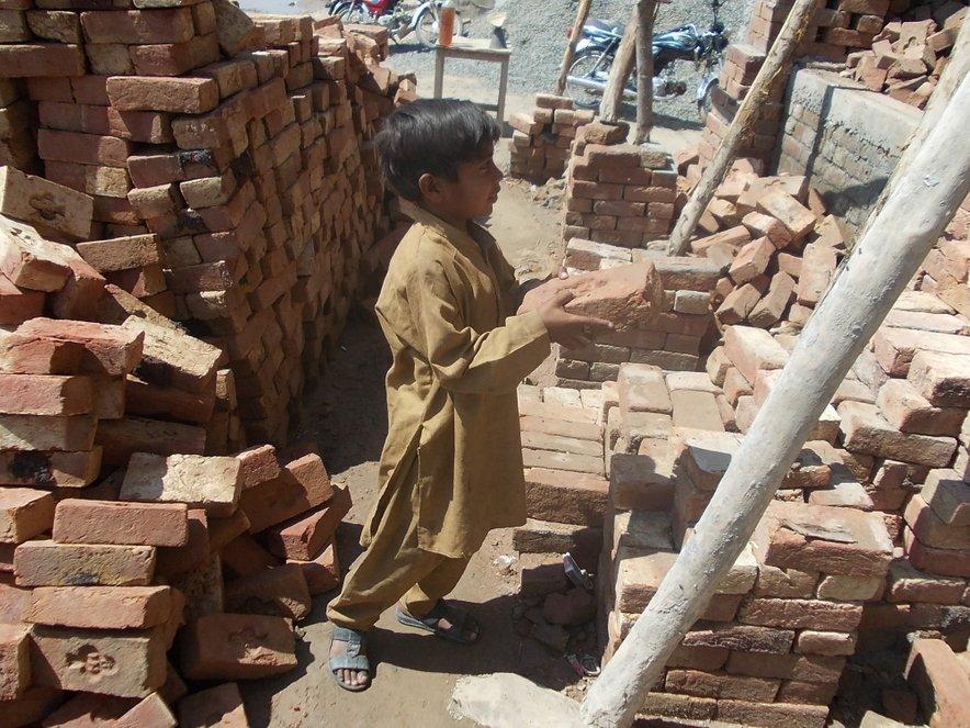 Deček gradi hišo v Pakistanu. Skoraj polovica od 160 milijonov otrok, ki so žrtve otroškega dela, je starih med pet in 11 let, več kot polovica jih opravlja nevarna dela.