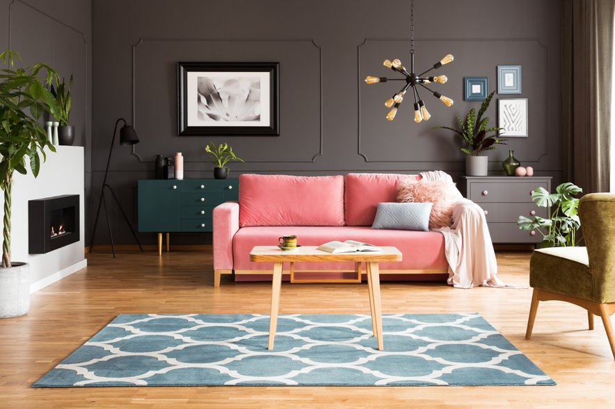 Temne stene se odlično podajo z rožnatim kavčem in svetlo modrim tepihom.
