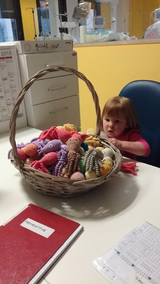 Najmanjša slovenska nedonošenka Erin ob košari s hobotnicami za nedonošenčke