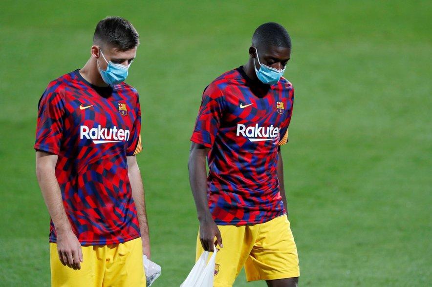 Francoska nogometaša Barcelone Clement Lenglet in Ousmane Dembele (desno) s klubsko majico za ogrevanje.