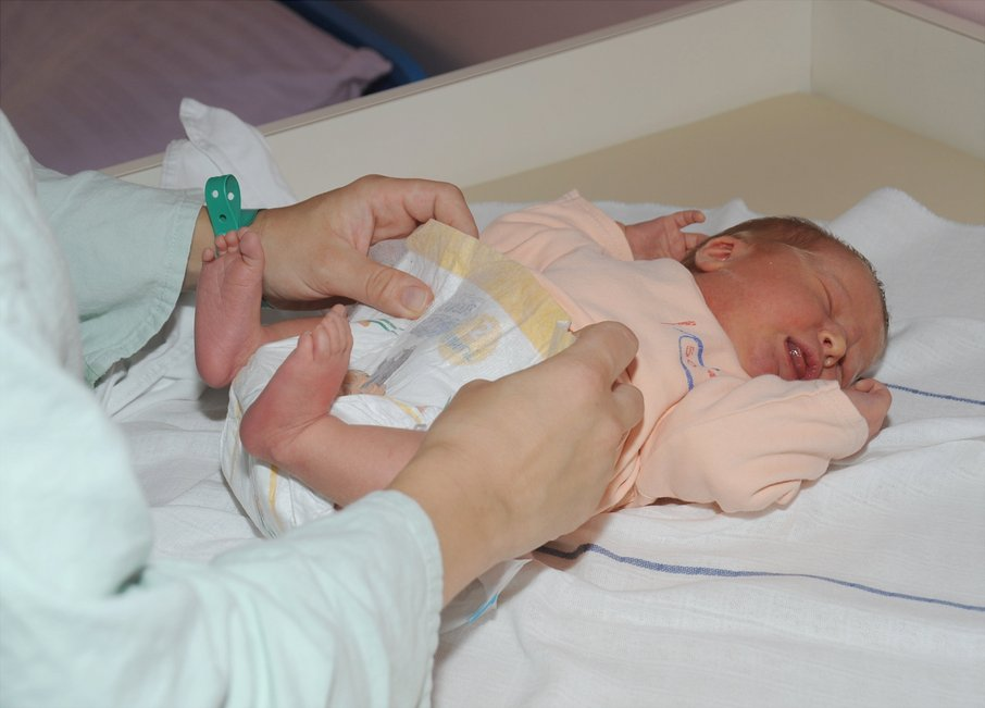 Mamica preoblači novorojenčka.